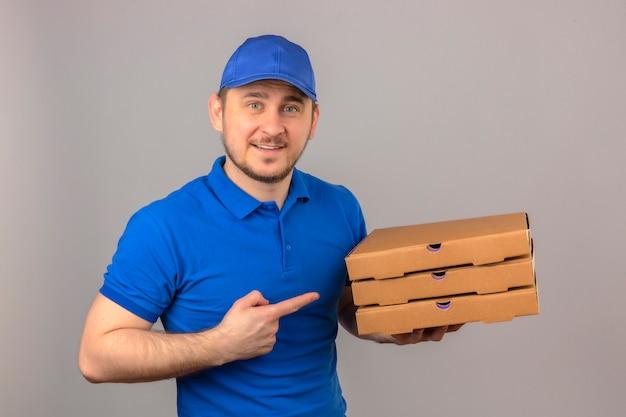 Młody człowiek dostawy ubrany w niebieską koszulkę polo i czapkę, trzymając stos pudełek po pizzy, wskazując palcem na nie patrząc na kamerę z uśmiechem stojąc na białym tle