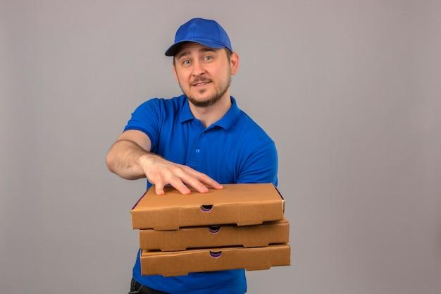 Młody człowiek dostawy ubrany w niebieską koszulkę polo i czapkę trzymającą wyciągający stos pudełek po pizzy patrząc na kamery z przyjaznym uśmiechem na białym tle