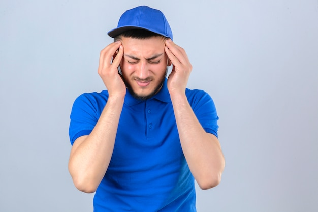 Młody człowiek dostawy ubrany w niebieską koszulkę polo i czapkę źle wyglądający dotykając głowy cierpiących na silny ból głowy na na białym tle