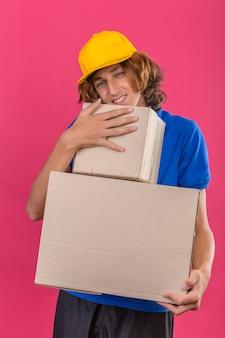 Młody człowiek dostawy ubrany w niebieską koszulkę polo i żółtą czapkę, trzymając kartony marzy obejmując pudełka uśmiechnięte z radosną buźką na odosobnionym różowym tle