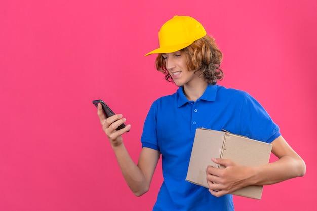 Młody człowiek dostawy ubrany w niebieską koszulkę polo i żółtą czapkę trzymający karton patrząc na ekran swojego smartfona z uśmiechem na twarzy stojącej na izolowanym różowym tle