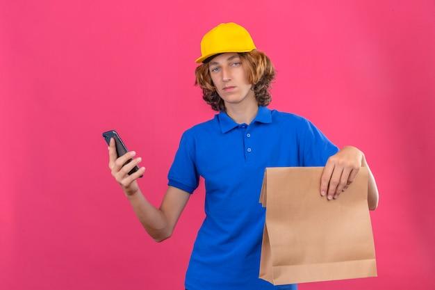Młody człowiek dostawy ubrany w niebieską koszulkę polo i żółtą czapkę trzymający papierowy pakiet i smartfon w rękach patrząc na aparat z uśmiechem na twarzy na na białym tle różowym tle