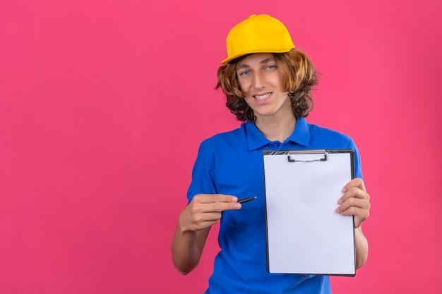 Młody człowiek dostawy ubrany w niebieską koszulkę polo i żółtą czapkę trzymający w rękach schowek i długopis z prośbą o podpis patrząc na kamery uśmiechnięty przyjaźnie na izolowanym różowym tle