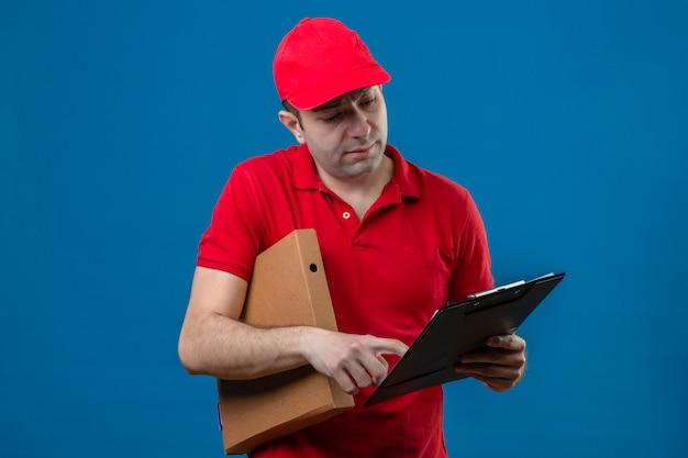 Młody człowiek dostawy w czerwonej koszulce polo i czapce patrząc w schowku w rękach czytania skoncentrowany na zadaniu stojącym nad izolowaną niebieską ścianą