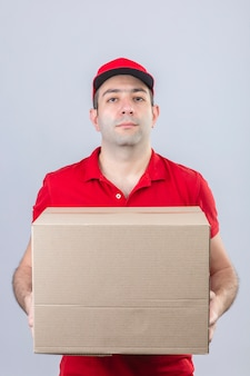 Młody człowiek dostawy w czerwonej koszulce polo i czapce, trzymając karton z poważną twarzą stojącą nad izolowaną białą ścianą
