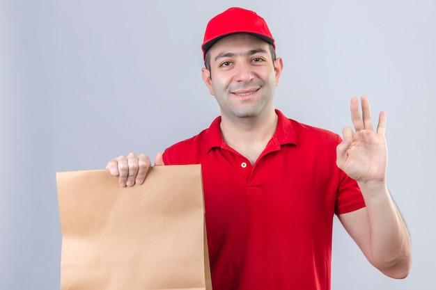 Młody człowiek dostawy w czerwonej koszulce polo i czapce, trzymając papierowy pakiet uśmiechnięty przyjacielski robi ok znak na białym tle ściany