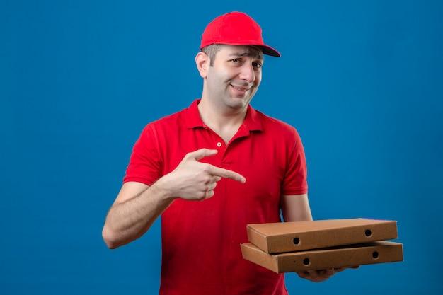 Młody człowiek dostawy w czerwonej koszulce polo i czapce, trzymając pudełko po pizzy i wskazując palcem na to z uśmiechem na twarzy nad odizolowaną niebieską ścianą