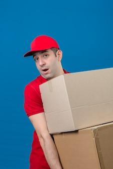 Młody człowiek dostawy w czerwonej koszulce polo i czapce, trzymający duży, ciężki karton, wyglądający na zaskoczonego dużym ciężarem nad odizolowaną niebieską ścianą