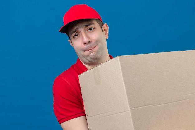 Młody człowiek dostawy w czerwonej koszulce polo i czapce trzymający duży, ciężki karton źle się czuje z powodu dużej wagi na odizolowanej niebieskiej ścianie
