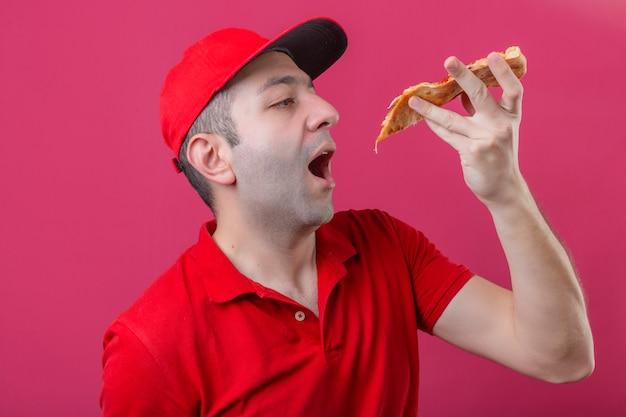 Młody człowiek dostawy w czerwonej koszulce polo i czapce zamierza ugryźć kawałek pizzy na izolowanej różowej ścianie