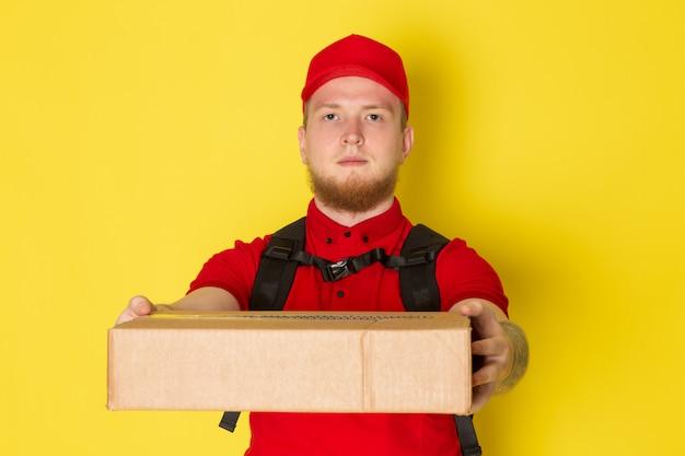 Młody człowiek dostawy w czerwonej polo czerwonej czapce białe dżinsy trzyma pudełko na żółtym