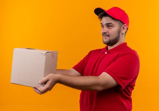 Młody człowiek dostawy w czerwonym mundurze i czapce, dając pakiet pudełko do klienta uśmiechnięty przyjazny
