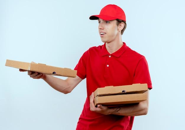 Młody człowiek dostawy w czerwonym mundurze i czapce daje pudełko po pizzy klientowi z uśmiechem na twarzy stojącej na białej ścianie