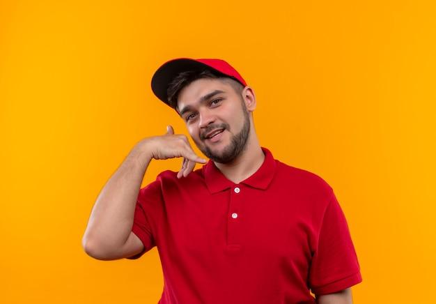 Młody człowiek dostawy w czerwonym mundurze i czapce, dzięki czemu zadzwoń do mnie gest z uśmiechem na twarzy