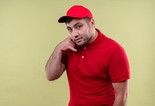 Młody człowiek dostawy w czerwonym mundurze i czapce dzwoniąc do mnie gestem uśmiechnięty pewnie stojąc nad zieloną ścianą