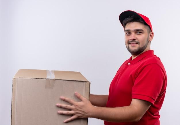Młody człowiek dostawy w czerwonym mundurze i czapce gospodarstwa pakiet polu patrząc na kamery z uśmiechem na twarzy