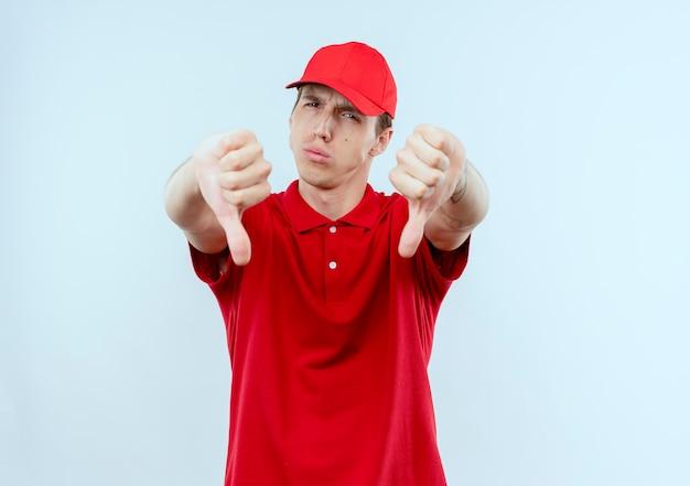 Młody człowiek dostawy w czerwonym mundurze i czapce patrząc do przodu niezadowolony, pokazując kciuki w dół stojąc na białej ścianie