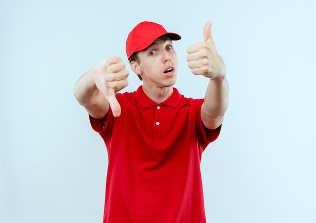 Młody człowiek dostawy w czerwonym mundurze i czapce patrząc do przodu zdezorientowany pokazując kciuki w górę iw dół stojąc na białej ścianie