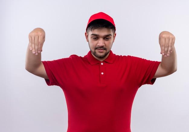Młody człowiek dostawy w czerwonym mundurze i czapce, patrząc pewnie, gestykulując rękami, koncepcja języka ciała