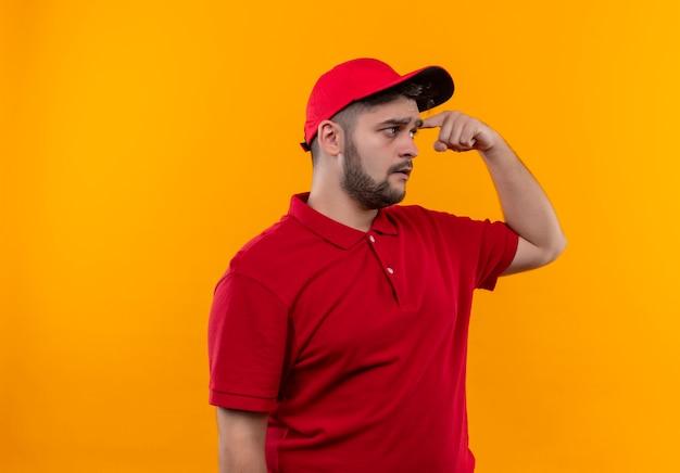 Młody człowiek dostawy w czerwonym mundurze i czapce, patrząc zdezorientowany, wskazując na jego skroń