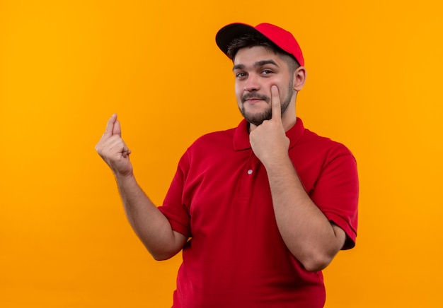 Młody człowiek dostawy w czerwonym mundurze i czapce pocierając palce wskazując na jego oko prosząc o pieniądze