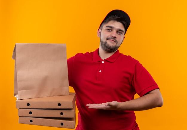 Młody człowiek dostawy w czerwonym mundurze i czapce prezentujący papierowe opakowanie i stos pudełek po pizzy wyglądający pewnie