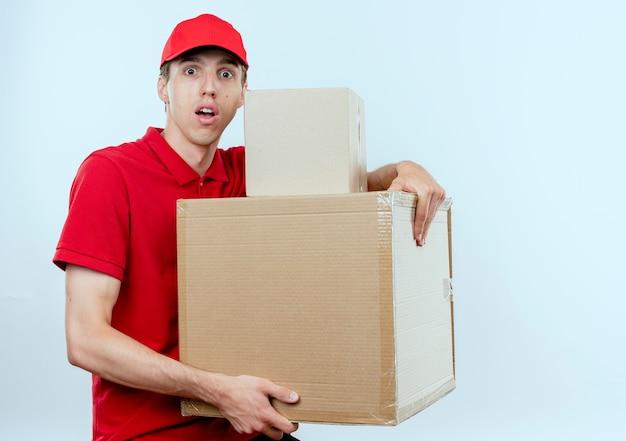Młody człowiek dostawy w czerwonym mundurze i czapce trzyma kartony patrząc do przodu, zmartwiony wyrazem strachu stojącym nad białą ścianą