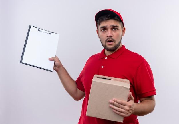 Młody człowiek dostawy w czerwonym mundurze i czapce trzyma pakiet pudełkowy pokazujący schowek z pustymi stronami wyglądającymi na zdezorientowanego i bardzo zaniepokojonego