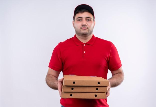 Młody człowiek dostawy w czerwonym mundurze i czapce trzyma pudełka po pizzy patrząc na kamery z pewnym siebie wyrazem stojącym na białej ścianie