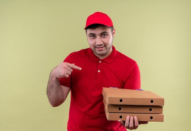 Młody człowiek dostawy w czerwonym mundurze i czapce trzyma pudełka po pizzy, wskazując palcem na nich, uśmiechając się pewnie stojąc nad zieloną ścianą