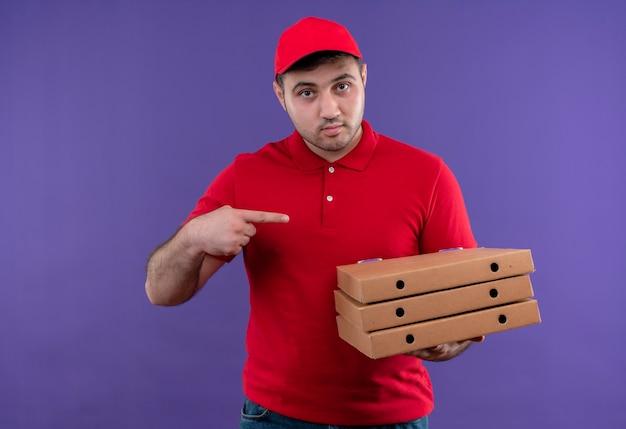 Młody człowiek dostawy w czerwonym mundurze i czapce trzyma pudełka po pizzy wskazując palcem na nie, patrząc pewnie stojąc nad fioletową ścianą