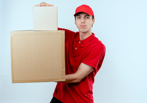 Młody człowiek dostawy w czerwonym mundurze i czapce, trzymając kartony patrząc do przodu z poważnym wyrazem twarzy stojącej na białej ścianie