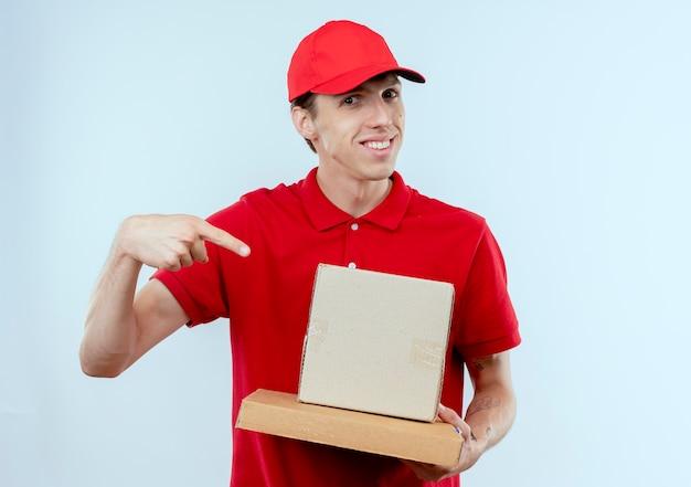 Młody człowiek dostawy w czerwonym mundurze i czapce, trzymając kartony, wskazując palcem wskazującym na nich, uśmiechając się pewnie stojąc na białej ścianie