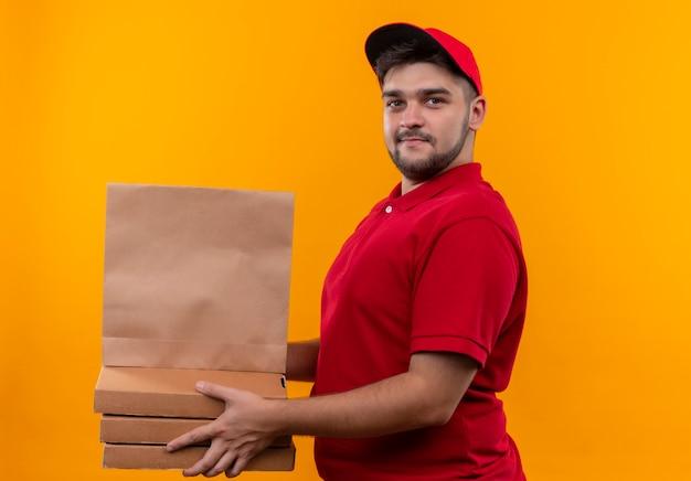Młody człowiek dostawy w czerwonym mundurze i czapce, trzymając pakiet papieru i stos pudełek po pizzy, patrząc pewnie