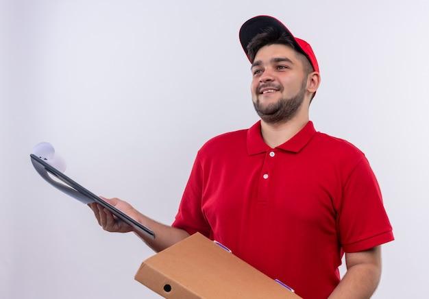 Młody człowiek dostawy w czerwonym mundurze i czapce, trzymając pakiet pole i schowek z pustymi stronami z prośbą o podpis