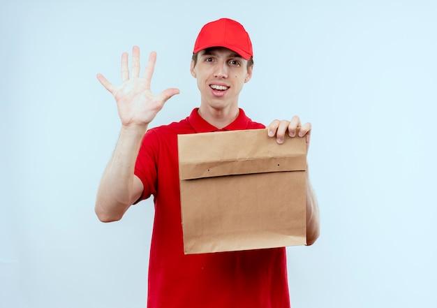 Młody człowiek dostawy w czerwonym mundurze i czapce trzymając papierowy pakiet pokazujący numer pięć uśmiechnięty pewnie stojący nad białą ścianą