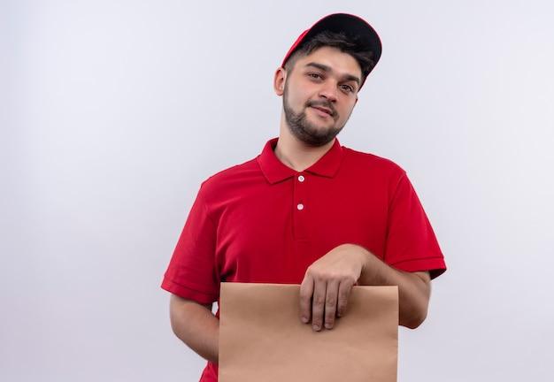 Młody człowiek dostawy w czerwonym mundurze i czapce, trzymając papierowy pakiet uśmiechnięty pewnie