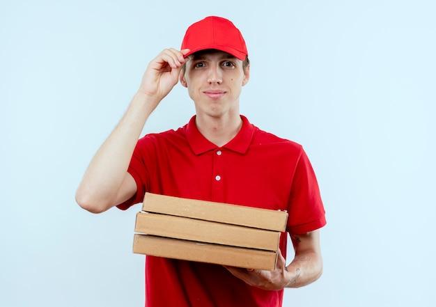 Młody człowiek dostawy w czerwonym mundurze i czapce, trzymając pudełka po pizzy patrząc do przodu z pewnym siebie wyrazem stojącym na białej ścianie