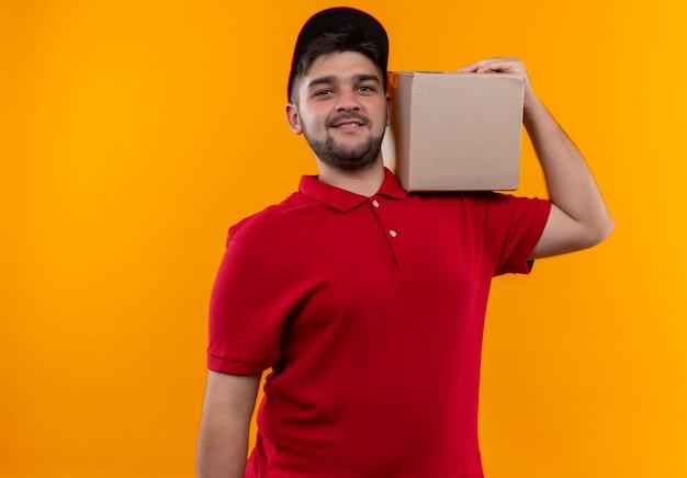 Młody człowiek dostawy w czerwonym mundurze i czapce, trzymając pudełko na ramieniu, patrząc pewnie