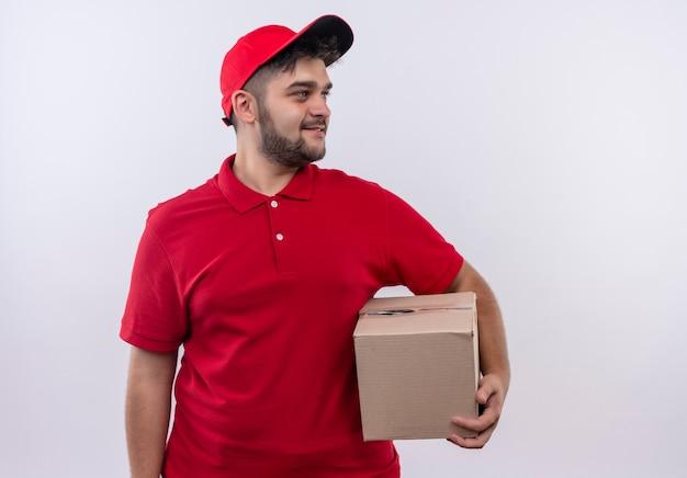 Młody człowiek dostawy w czerwonym mundurze i czapce, trzymając pudełko pakiet patrząc na bok uśmiechnięty pewnie