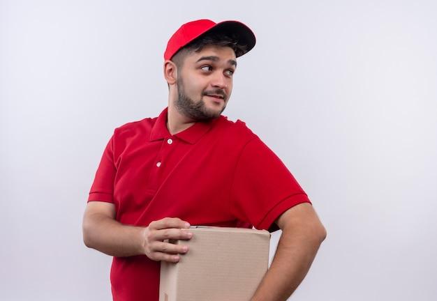 Młody człowiek dostawy w czerwonym mundurze i czapce, trzymając pudełko pakiet patrząc z uśmiechem na twarzy