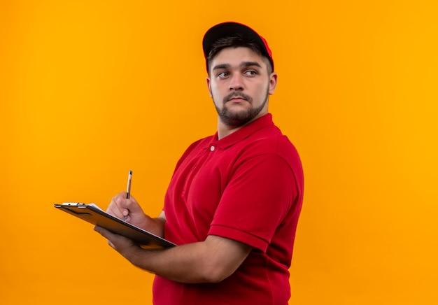 Młody człowiek dostawy w czerwonym mundurze i czapce, trzymając schowek z piórem, patrząc na bok z poważną miną