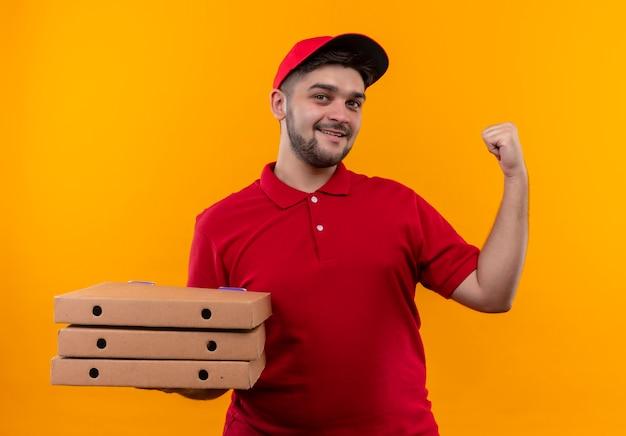Młody człowiek dostawy w czerwonym mundurze i czapce, trzymając stos pudełek po pizzy, patrząc pewnie i uśmiechając się, wskazując do tyłu