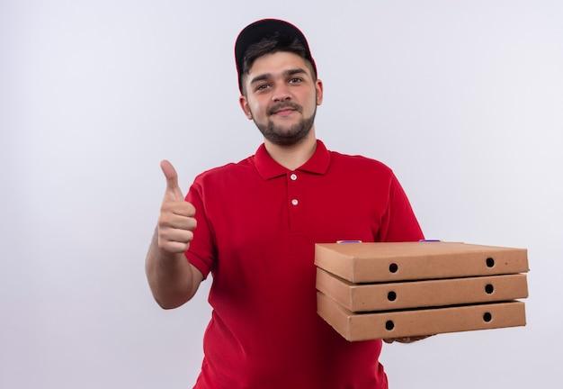 Młody człowiek dostawy w czerwonym mundurze i czapce, trzymając stos pudełek po pizzy, patrząc pewnie, uśmiechnięty pokazując kciuki do góry