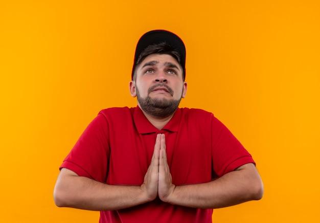 Młody człowiek dostawy w czerwonym mundurze i czapce trzymający dłonie razem w geście modlitwy, prosząc z wyrazem nadziei bardzo emocjonalny i zmartwiony