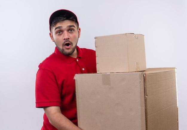 Młody człowiek dostawy w czerwonym mundurze i czapce trzymający duże kartony wyglądający na zaskoczonego i zdumionego