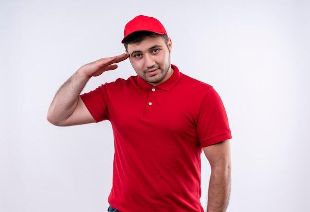 Młody człowiek dostawy w czerwonym mundurze i czapce, uśmiechając się pewnie salutując stojąc na białej ścianie