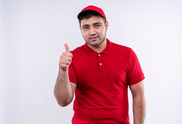 Młody człowiek dostawy w czerwonym mundurze i czapce uśmiechnięty radośnie pokazując kciuki stojąc na białej ścianie