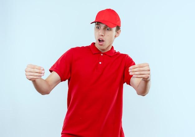 Młody człowiek dostawy w czerwonym mundurze i czapce wygląda zdziwiony, gestykuluje rękami, koncepcja języka ciała stoi na białej ścianie