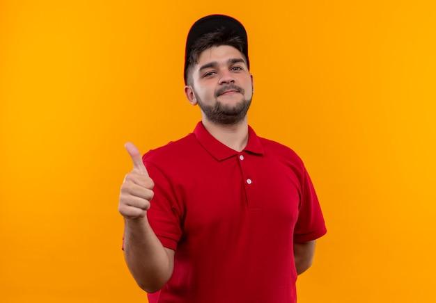 Młody człowiek dostawy w czerwonym mundurze i czapce z uśmiechem pokazując kciuk do góry
